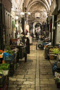 Una donna mussulmana fa acquisti nel souk arabo di Gerusalemme
