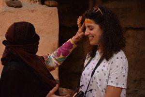 Una donna applica un unguento di zafferano sulla fronte di Rossana in Oman