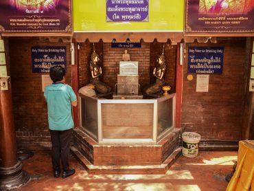 Un fedele in preghiera presso il tempio Wat Intharawihan